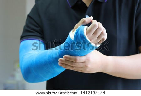 Closeup of asian man's arm with long arm plaster, fiberglass cast therapy cover by blue elastic bandage after sport accident. Appropriate treatment in western medicine.