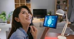 closeup of asian young woman using smart home app with voice assistant to control light turning on with tablet pc