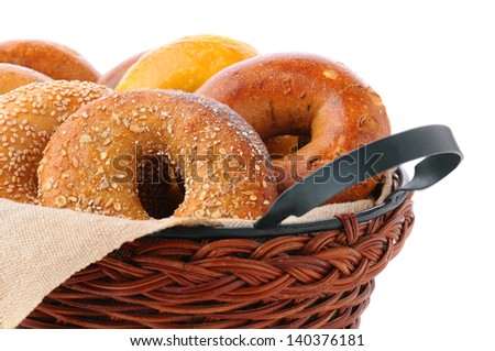 Closeup of assorted fresh bagels in a basket, including egg, sesame seed, multi-grain, plain, and cinnamon raisin.