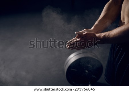 Closeup of athlete clapping hands before lifting barbells