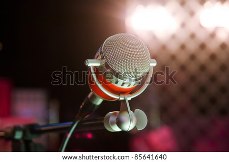 Closeup of audio microphone on stage background - stock photo