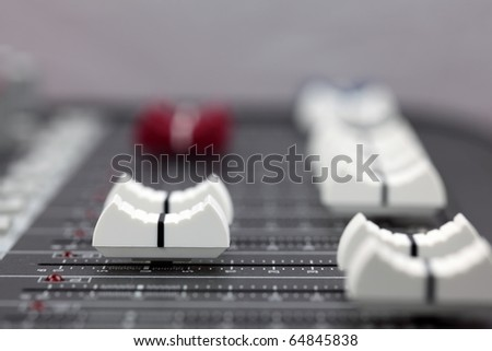 Closeup of audio mixing console. Shallow depth of field. Studio work.