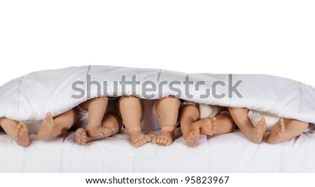 Closeup of Baby Doll 's bare feet in bed isolated on white