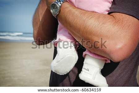 Closeup of Baby in Adorable Boots at the Beach in Daddy's Arms