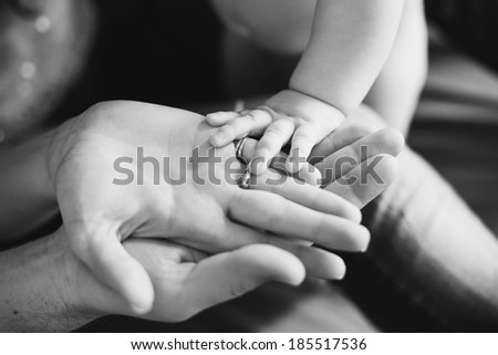 Closeup of baby's and parent's hands. black and white picture