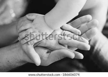 Closeup of baby\'s and parent\'s hands. black and white picture