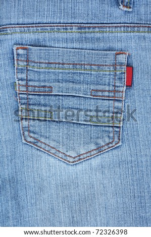 Closeup of back blue jeans pocket with colourful stitches.