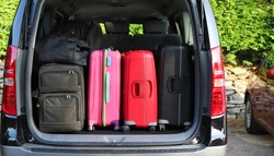 Closeup of back, rear side of black van car carrying  luggages, suitcases preparing for lovely family holiday with natural background in bright sunny day.