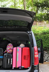 Closeup of back, rear side of black van car carrying  luggages, suitcases preparing for lovely family holiday with natural background in sunny day. Vertical view.