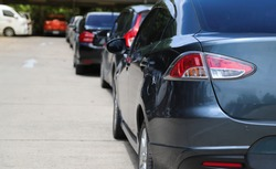 Closeup of back, rear side of dark blue sedan car and other cars parking in outdoor parking area in sunny day.