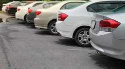 Closeup of back, rear side of silver sedan car and other cars parking in outdoor parking area in sunny day.