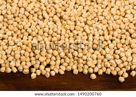 Closeup of background with raw garbanzo grains  on wooden  surface, healthy and nutritious food