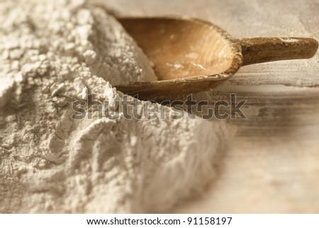 Closeup of baking powder and a wooden scoop