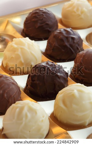 Closeup of  ball-shaped chocolates made with black chocolate, white chocolate and milk chocolate