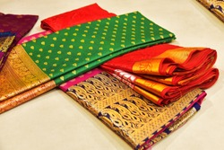 Closeup of Banares silk saris in a textile shop, displayed in front of customers. These exquisite, expensive sarees are famous for their gold and silver zari, brocade. Incredible India.