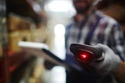 Closeup of bar code reader in hand of unrecognizable warehouse worker doing inventory of stock