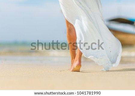 Closeup of barefoot female young adult lower body relaxing in ocean water on summer holiday