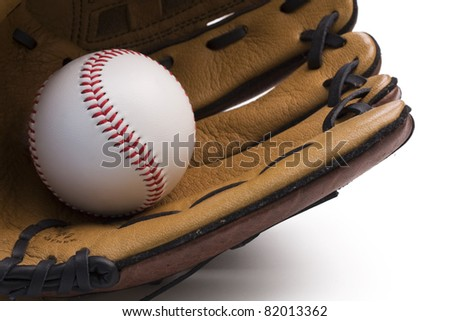 Closeup of baseball glove holding baseball on white background.