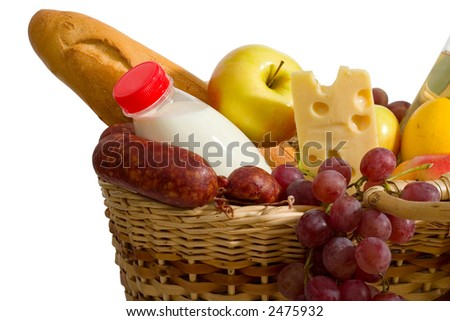 closeup of basket with some food - apples, milk, cheese, bread, grapes etc. Isolated on white background