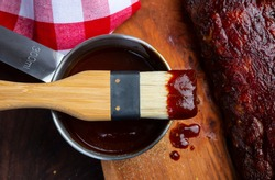 Closeup of basting brush with Barbecue sauce over ribs