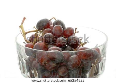 Closeup of batch of black seedless grapes in clear glass bowl against white background.