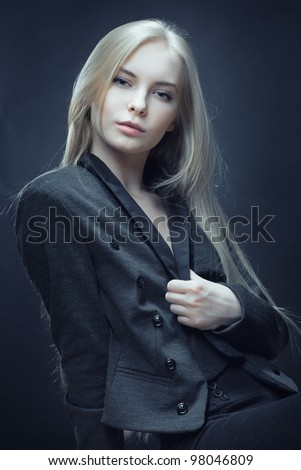 closeup of beautiful blonde woman in coat on dark background