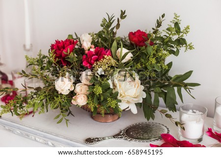 Closeup of beautiful bouquet of fresh flowers of red, white, pink, pastel colors in vintage golden vase. Home interior decorated with floral composition and petals. Horizontal color photography. #658945195
