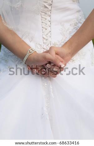 Closeup of beautiful bride's hands on wedding dress