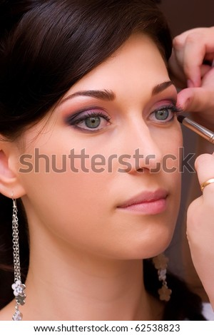 closeup of beautiful brunette young lady profile prepared for the event by makeup artist