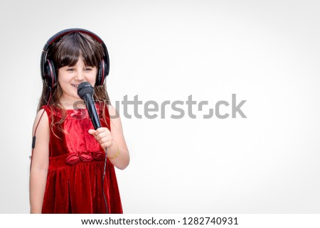Closeup of beautiful happy smiley long hair child girl wearing red dress and headphones . Small singer Girl holding black microphone singing songs with white background texture #1282740931