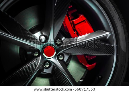 Closeup of beautiful Large Alloy wheel of expensive supercar having painted break callipers and large disc brake