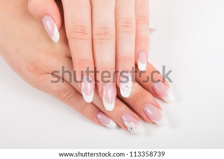 Closeup of beautiful nails with french manicure on white background