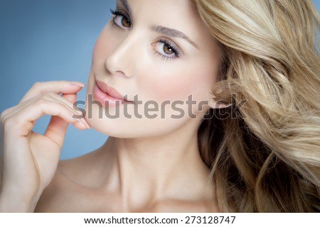 Closeup of beautiful natural blond woman with glowing skin over blue background. #273128747