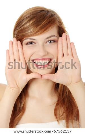 Closeup of beautiful smiling teen woman making frame on her face with her hands