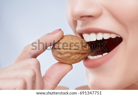 Closeup of beautiful snow-white smile. Ideal strong white teeth, teethcare. Healthcare, stomatological concept for dentists. Only smile, walnut in a mouth