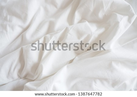 Closeup of beautiful white shiny crumpled polyester fabric sheets on the bed with warm motion and feeling for background and decoration. Cloth washing and laundry concept at home #1387647782
