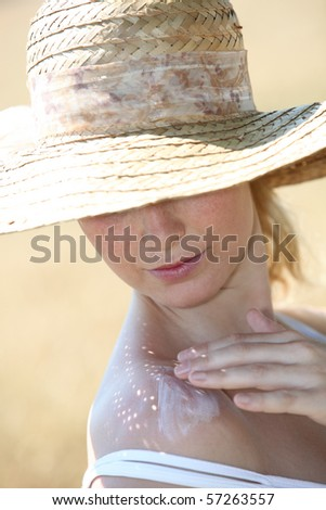 Closeup of beautiful woman spreading sunscreen on her shoulder