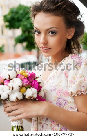 Closeup of beautiful woman with bouquet of flowers. Outdoors