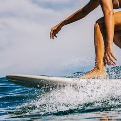 Closeup of beautiful young Sporty girl in a bikini swimsuit ride big wave with lot of splashes. Fit surfer woman surfing in Mauritius in the Indian Ocean on the transparent waves. Outdoor Active Life.