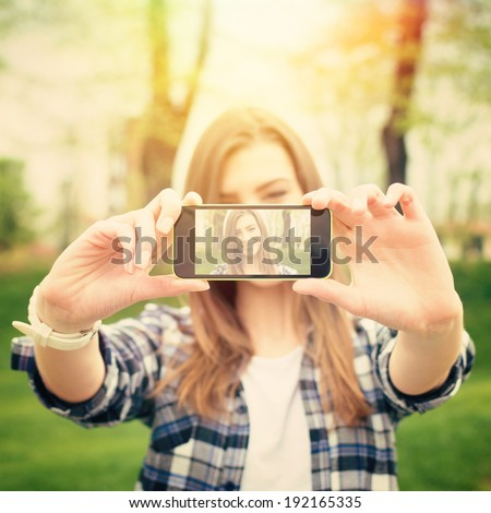 Closeup of beautiful young woman taking a selfie photo with smart phone outdoors on sunny summer day. Instant filter. Square image.