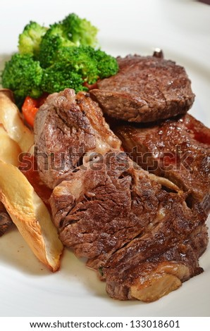 Closeup of beefsteak  with french fries and vegetables
