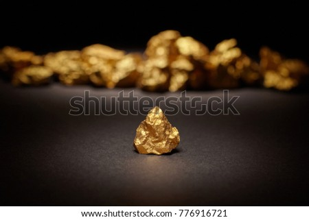 Closeup of big gold nugget on a black background stock photo