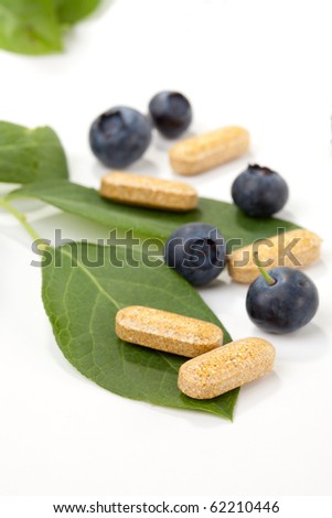 Closeup of bilberry extract pills and fresh berries and leaves best suited for alternative medicine ads