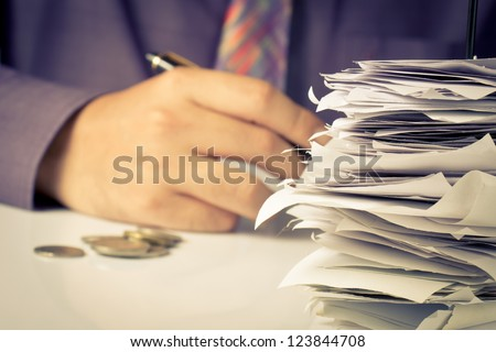 Closeup of bills in paper nail with hand calculating