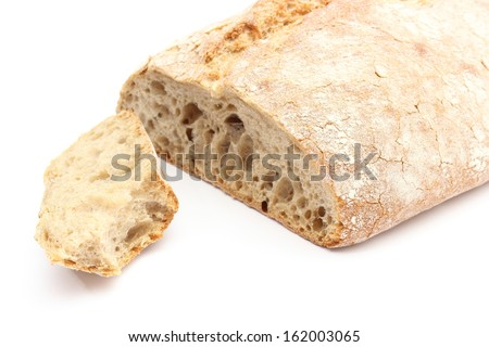 Closeup of bitten slice of rye bread and loaf bread. Isolated on white background