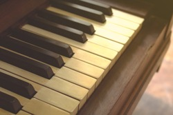 Closeup of black and white piano keys and wood grain with vintage tone