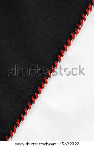Closeup of black and white textile material jointed by red thread seam