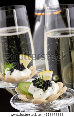 Closeup of black caviar on Creme Fraiche and flutes of Champagne over black background