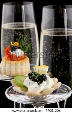 Closeup of black caviar on Creme Fraiche and smoked salmon canape and flutes of Champagne over black background.