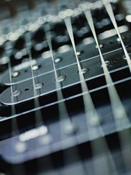 closeup of black electric guitar and pickups. Vertical shape, studio shot, selective focus